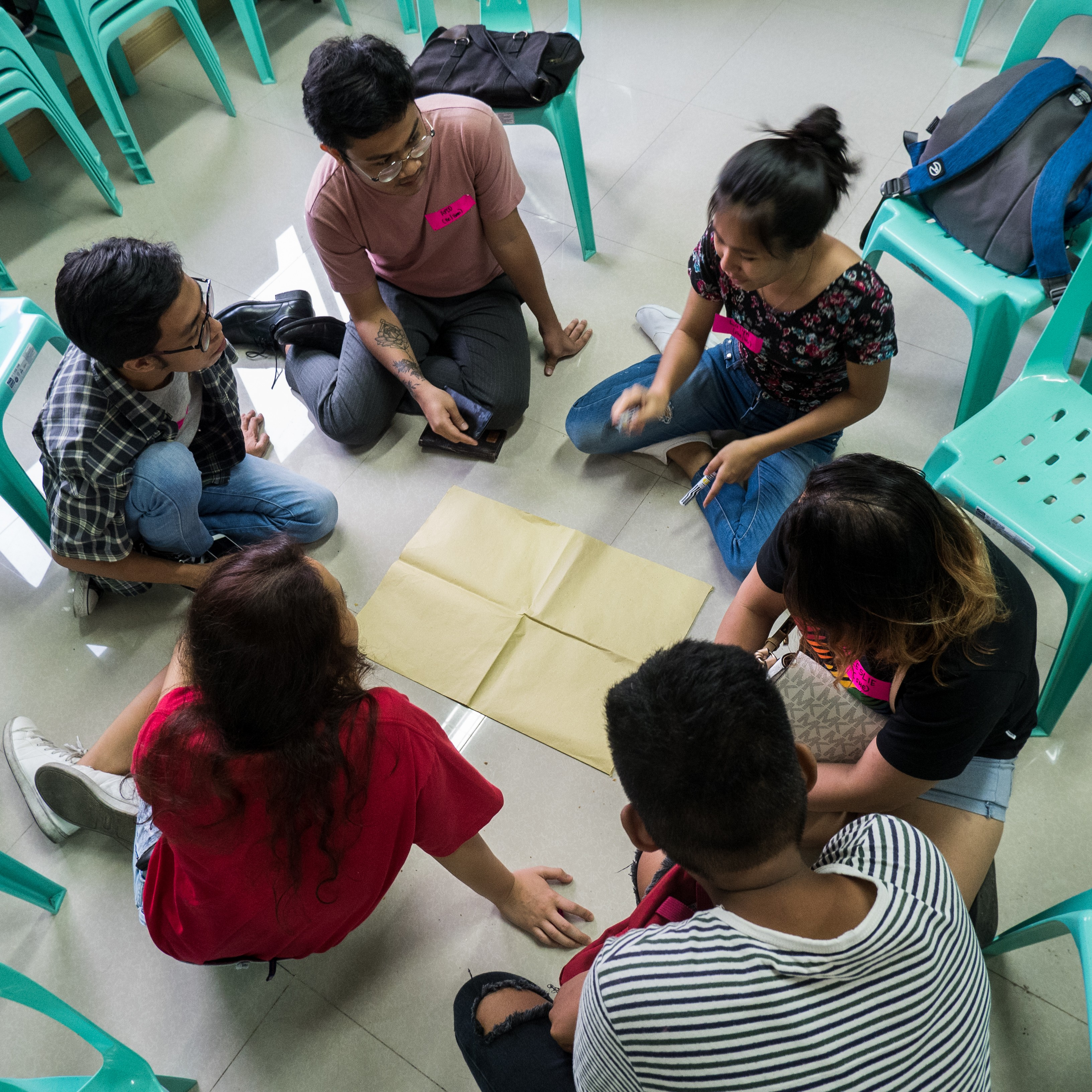 Image: Six people are in the middle of a conversation. They are seated on a floor, with a flat sheet of manila paper in between them.