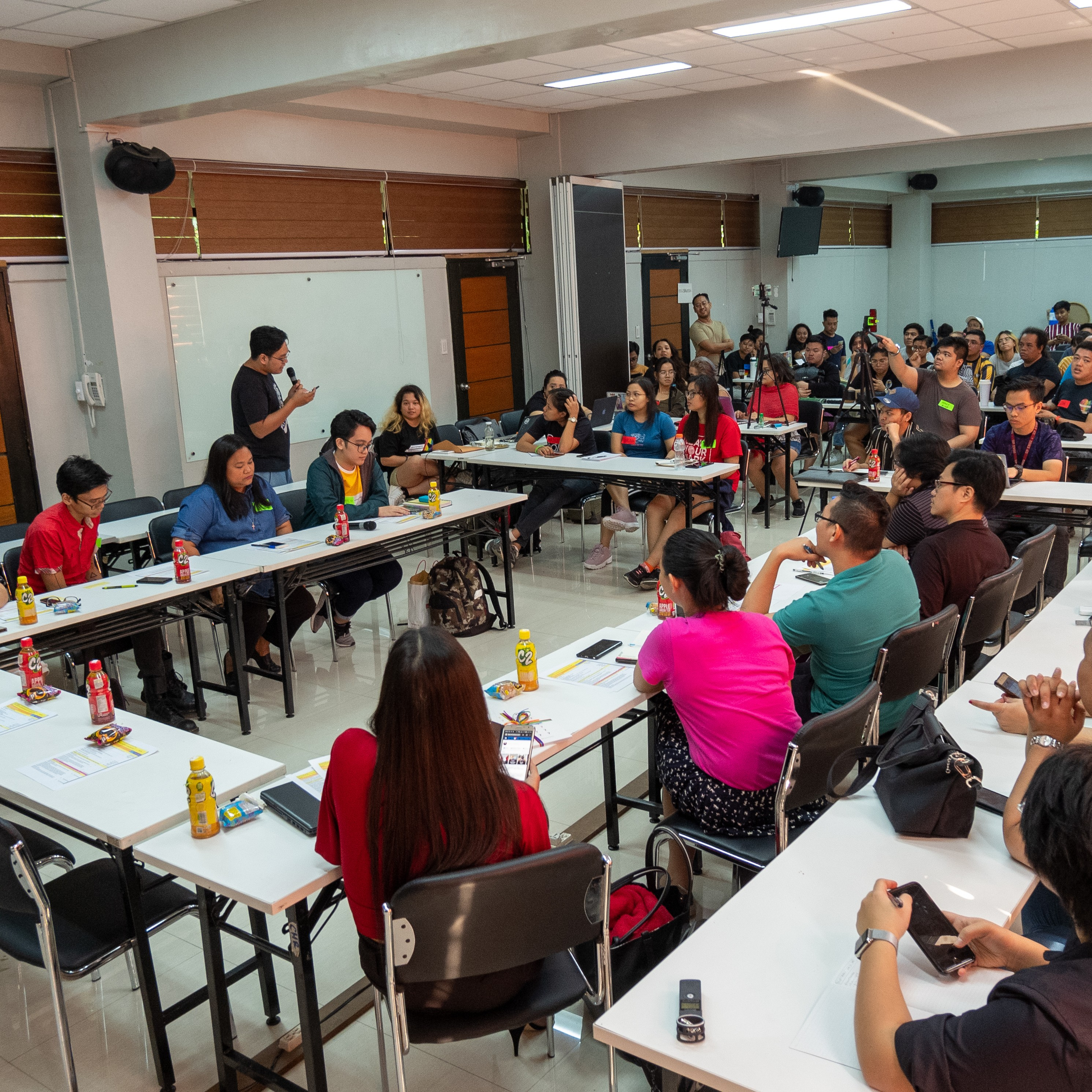 Image: The inside of a room full of attendees from the round table discussion 'How did Pride resistance in the Philippines start?' in 2019. Tables are arranged in a closed rectangle, occupied by LGBTQIA+ activists from various organizations, talking about the history of Pride in the Philippines.