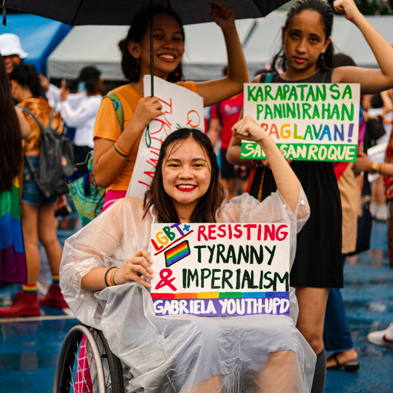 Image: Three people raising their left fists to the air. In the foreground, a wheelchair user wearing a raincoat smiles and looks to the camera. They hold a placard that says 'LGBT+ RESISTING TYRANNY & IMPERIALISM' and 'GABRIELA YOUTH-UPD' under it. Behind them to the right, a person wearing a black dress is looking to the camera and holding up a placard that says 'KARAPATAN SA PANINIRAHAN IPAGLAVAN!' and 'SAVE SAN ROQUE' under it. To their left, a person wearing a yellow shirt is smiling widely and holding another placard and a black umbrella in their right hand.