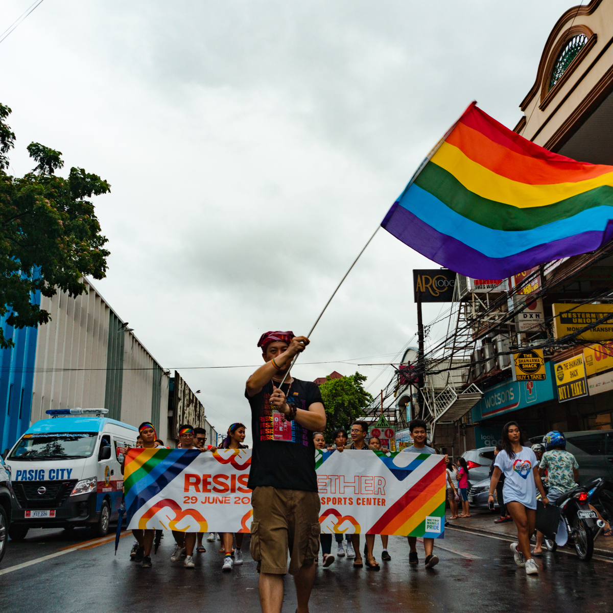 Image: A wide shot of the front of a parade. A Pride March marshal raises a rainbow flag, followed by a large crowd holding a tarpaulin that reads 'RESIST TOGETHER'.