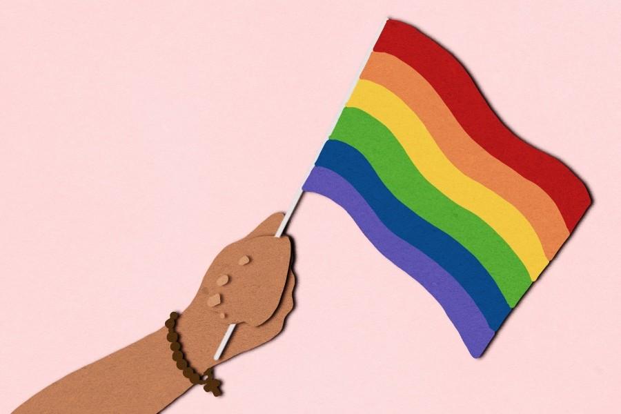 A brown arm waving a rainbow flag