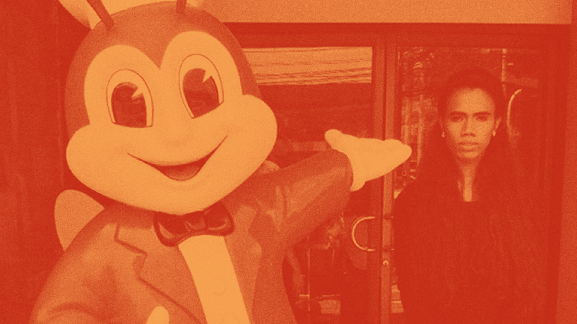An image of a Jollibee statue pointing at Bunny Carandag, awash in orange.